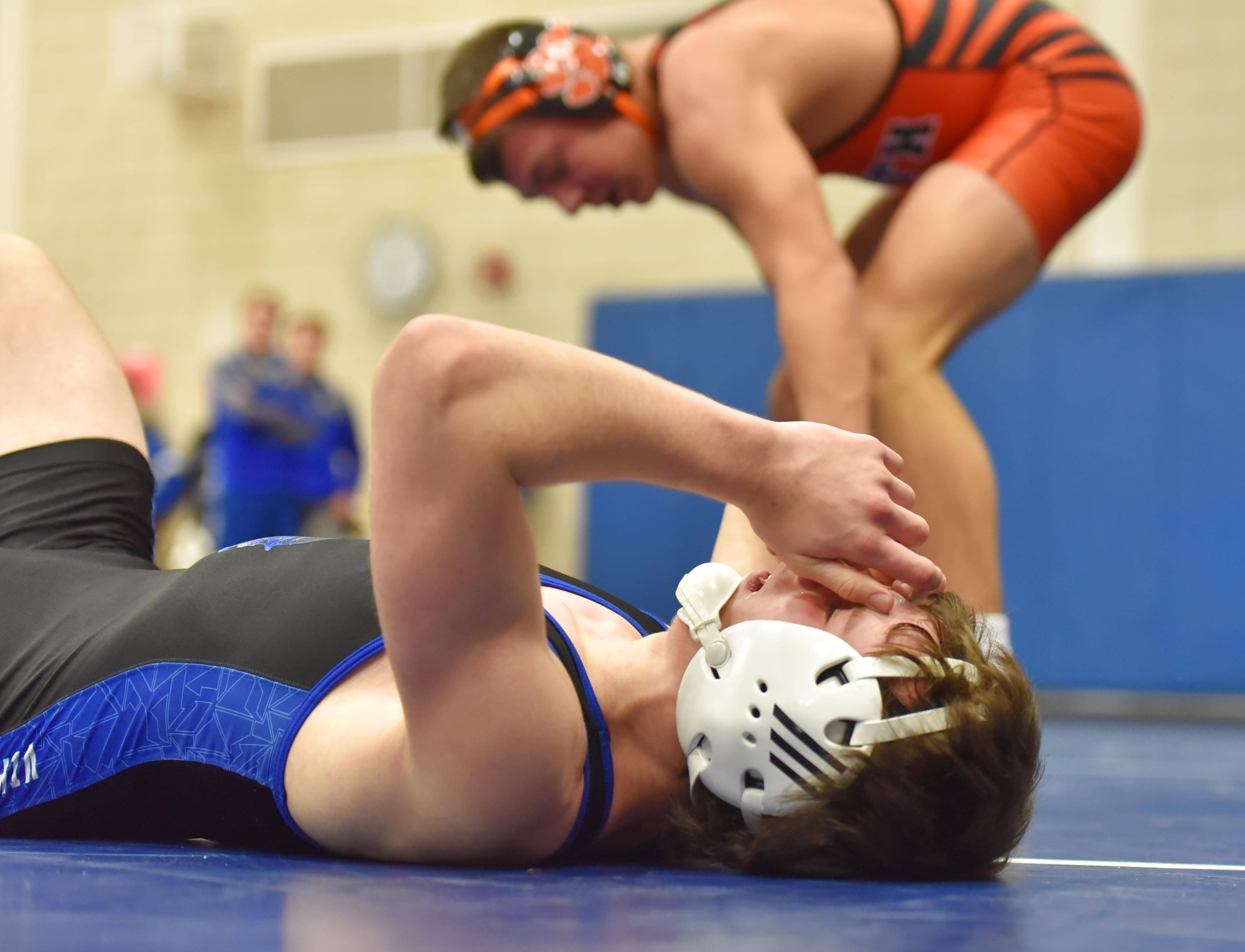 Geneva's Ian Puck covers his face after being pinned by Wheaton Warrenville South's Aidan Waszak in the 120-pound semifinal bout at the Jim Newbill Wrestling Invitational at Geneva High School Saturday.