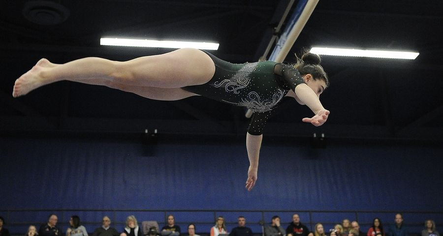 Glenbard West Maddie Diab dismounts the balance beam at the Naperville North girls gymnastics invite at Naperville North High School on Saturday.