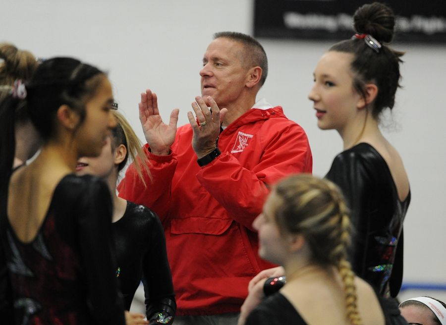 Naperville Central's Glen Reimers retires as coach and teacher at Naperville Central after 33 years seen here with his girls gymnastics team at the Naperville North girls gymnastics invite at Naperville North High School on Saturday.
