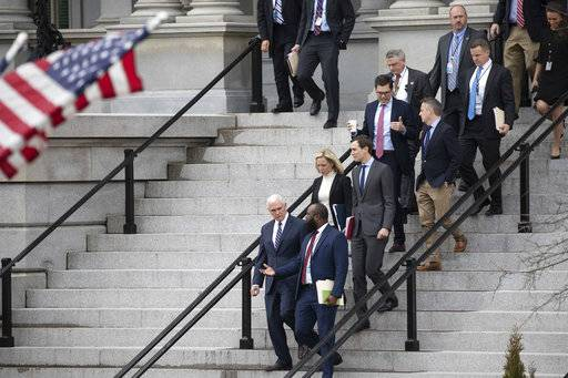 Vice President Mike Pence, left, White House legislative affairs aide Ja'Ron Smith, Homeland Security Secretary Kirstjen Nielsen, second row left, White House Senior Adviser Jared Kushner, and others, walk down the steps of the Eisenhower Executive Office building, on the White House complex, after a meeting with staff members of House and Senate leadership, Saturday, Jan. 5, 2019, in Washington.