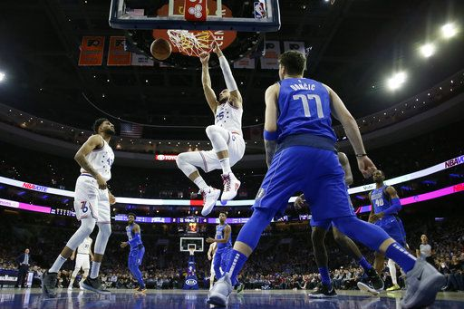 Philadelphia 76ers' Ben Simmons (25) hangs on the rim after a dunk as Jonah Bolden (43) and Dallas Mavericks' Luka Doncic (77) look on during the first half of an NBA basketball game, Saturday, Jan. 5, 2019, in Philadelphia.