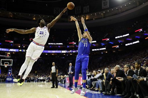 Dallas Mavericks' Luka Doncic (77) tries to get a shot past Philadelphia 76ers' Joel Embiid (21) during the first half of an NBA basketball game, Saturday, Jan. 5, 2019, in Philadelphia.