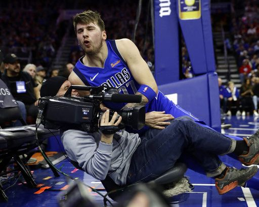 Dallas Mavericks' Luka Doncic, top, crashes into a television cameraman after falling out of bounds during the first half of an NBA basketball game against the Philadelphia 76ers, Saturday, Jan. 5, 2019, in Philadelphia.