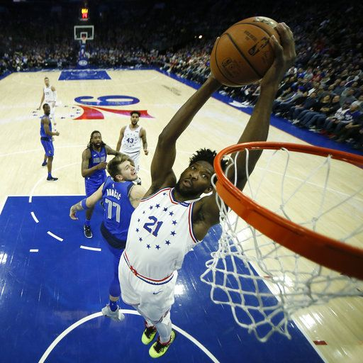 Philadelphia 76ers' Joel Embiid (21) goes up for a dunk past Dallas Mavericks' Luka Doncic (77) during the first half of an NBA basketball game, Saturday, Jan. 5, 2019, in Philadelphia.