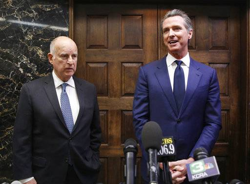 FILE- In this Nov. 13, 2018 file photo California Gov.-elect Gavin Newsom, right, and Gov. Jerry Brown talk with reporters after their meeting at the Capitol, Tuesday, Nov. 13, 2018, in Sacramento, Calif. Newsom will be sworn in to office Jan. 7, 2019, concluding the 80-year-old Brown's four terms.