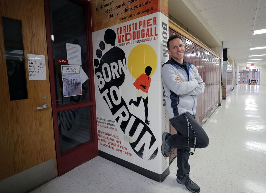 Mundelein High School English teacher Ryan Buck stands near the entrance to his classroom, where vinyl murals reproducing book jackets now decorate the walls. The murals have generated a buzz over social media.