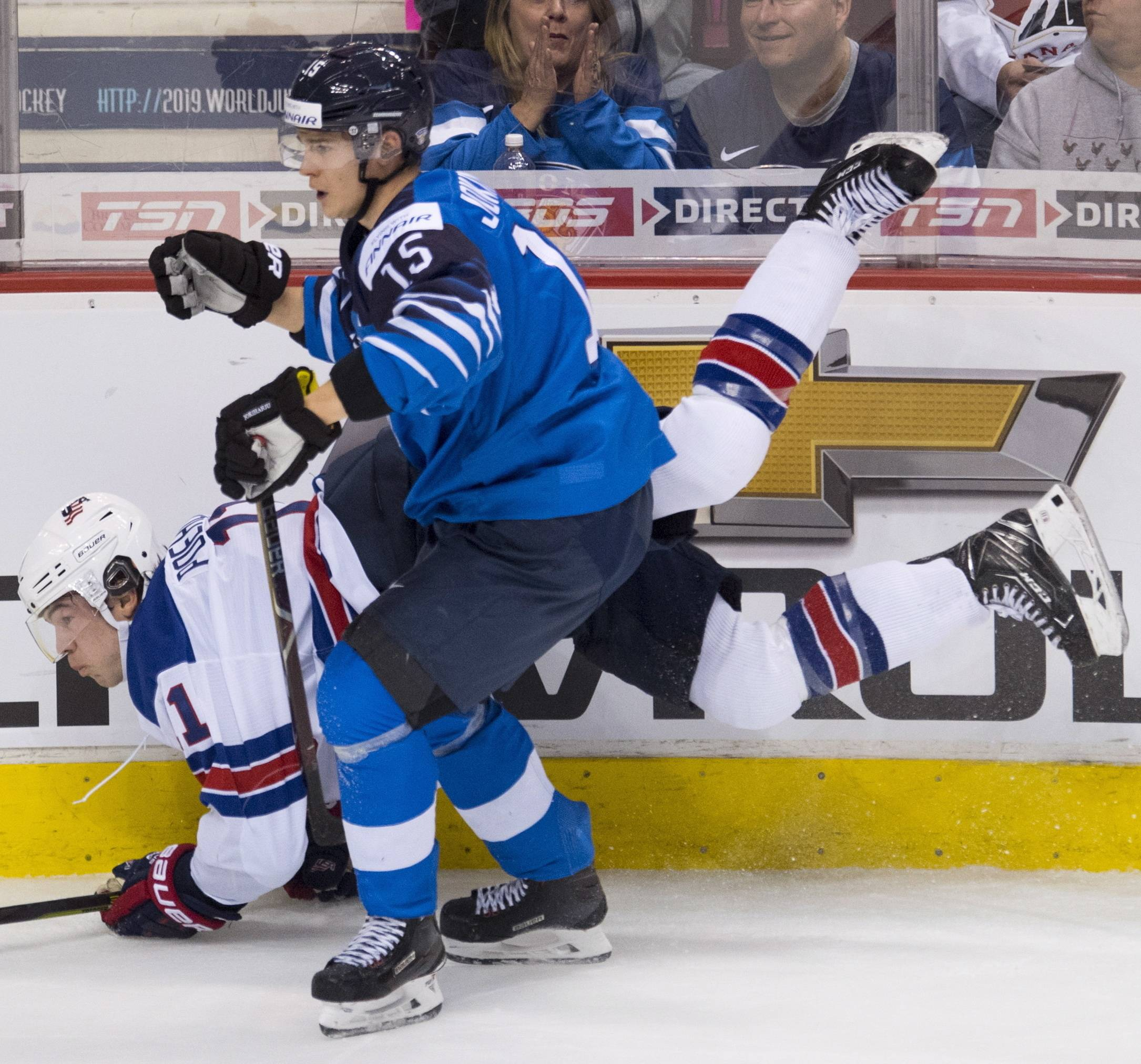 United States' Ryan Poehling goes into the boards with Finland's Henri Jokiharju during the first period of the gold medal game at the world junior hockey tournament, Saturday, Jan. 5, 2019 in Vancouver, British Columbia.