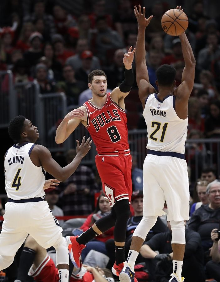 Chicago Bulls guard Zach LaVine, center, passes against Indiana Pacers guard Victor Oladipo, left, and forward Thaddeus Young during the first half of an NBA basketball game Friday, Jan. 4, 2019, in Chicago.