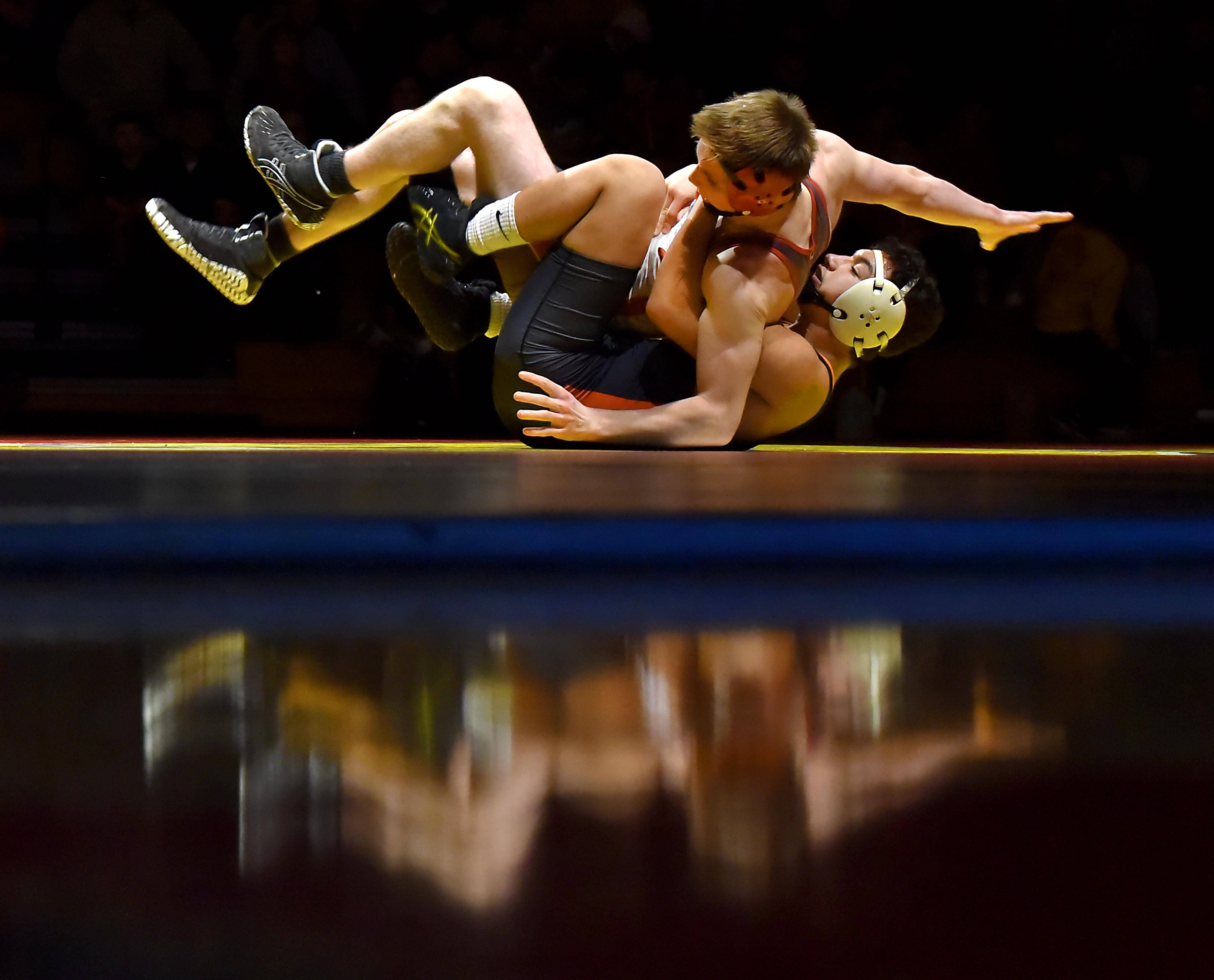 Reflected in the glossy gym floor, St. Charles East's Charles Falka rolls back with Batavia's Andy Posledni in his grasp in their 145-pound match Thursday in a wrestling match in Batavia.