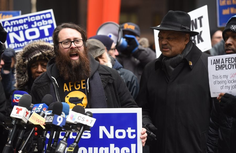With the Rev. Jesse Jackson beside him, Matt Muchowski of the American Federation of Government Employees speaks during a rally against the government shutdown Thursday at Federal Plaza in Chicago.