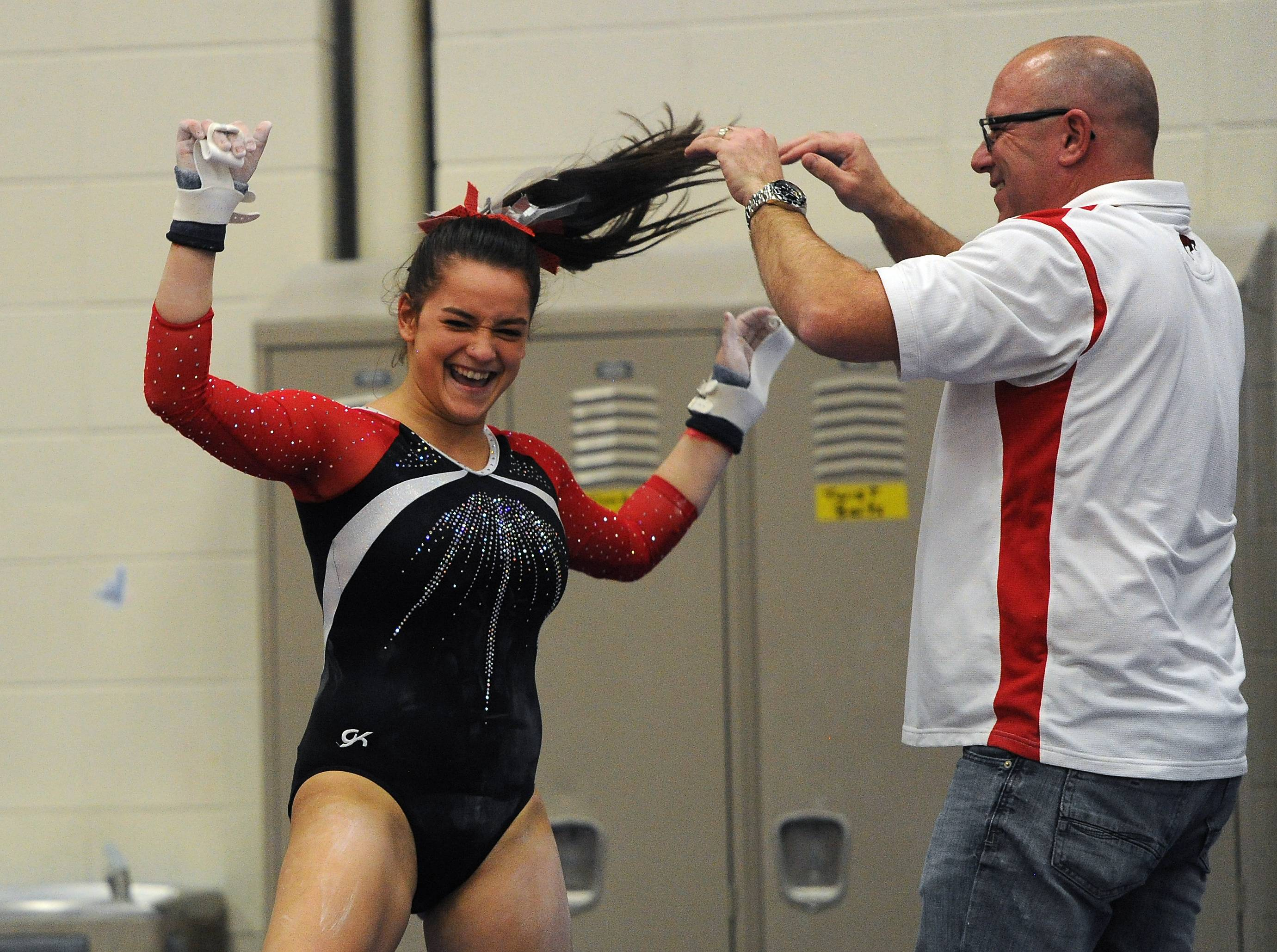 Barrington's Ashley Diaz celebrates with her coach Jason Loeffler after her routine on the uneven bars in the MSL. varsity girls gymnastics triangular meet in Barrington on Thursday.