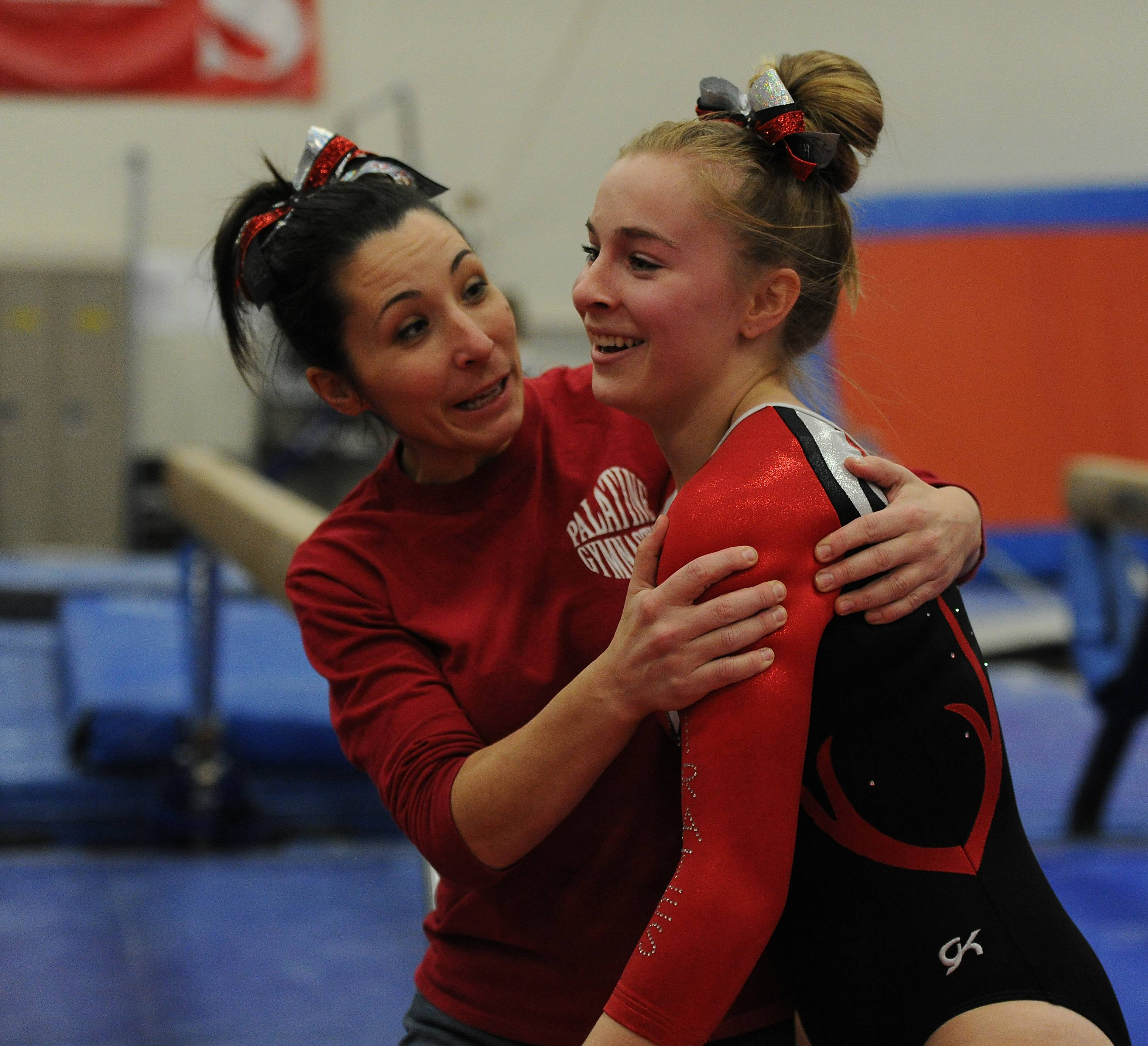 Palatine's Samantha Mogensen celebrate with her coach Kathy Blaheta after her routine on the beam in the MSL. varsity girls gymnastics triangular meet in Barrington on Thursday.