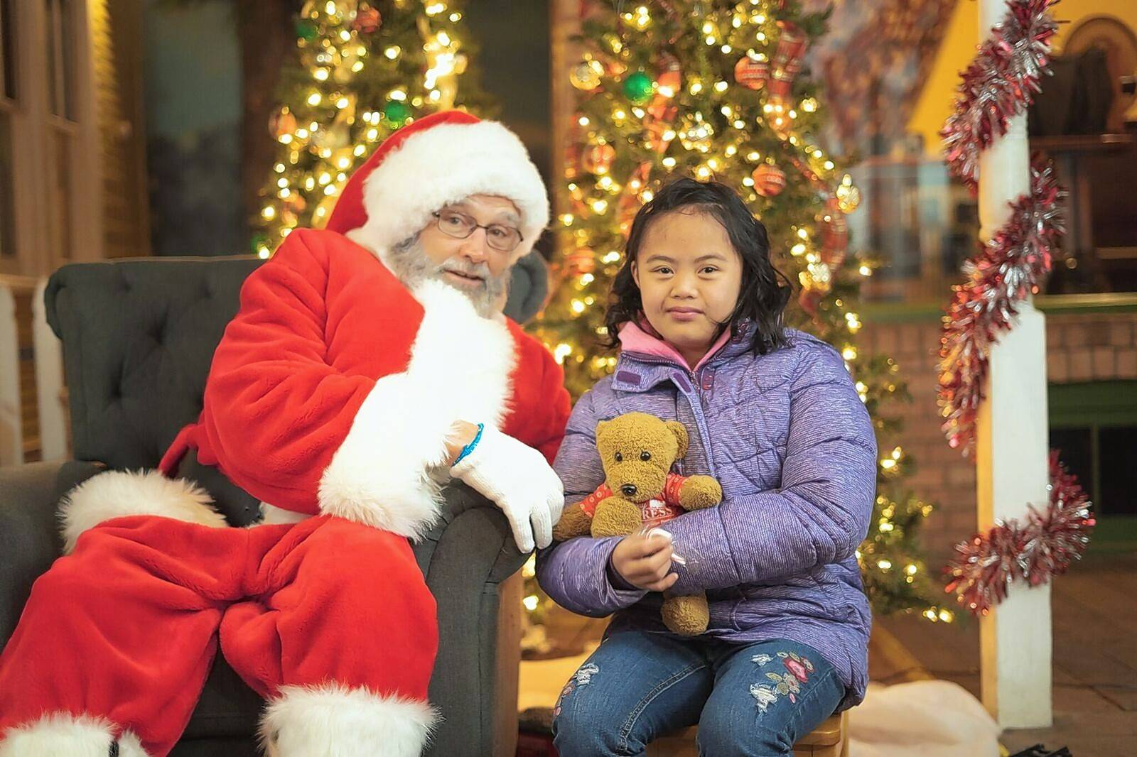 Santa Claus learns what Grace Valzado would like to have under her Christmas tree at the recent Holiday Express Special Needs Night at Blackberry Farm in Aurora.