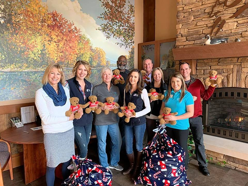 Quality Logo Products representatives Kate Oscarson, second from left, and Kelsey Skager along with other Fox Valley District employees gather together to drop off the company's 250 donated teddy bears and place them in bags for the Holiday Express Special Needs Night.