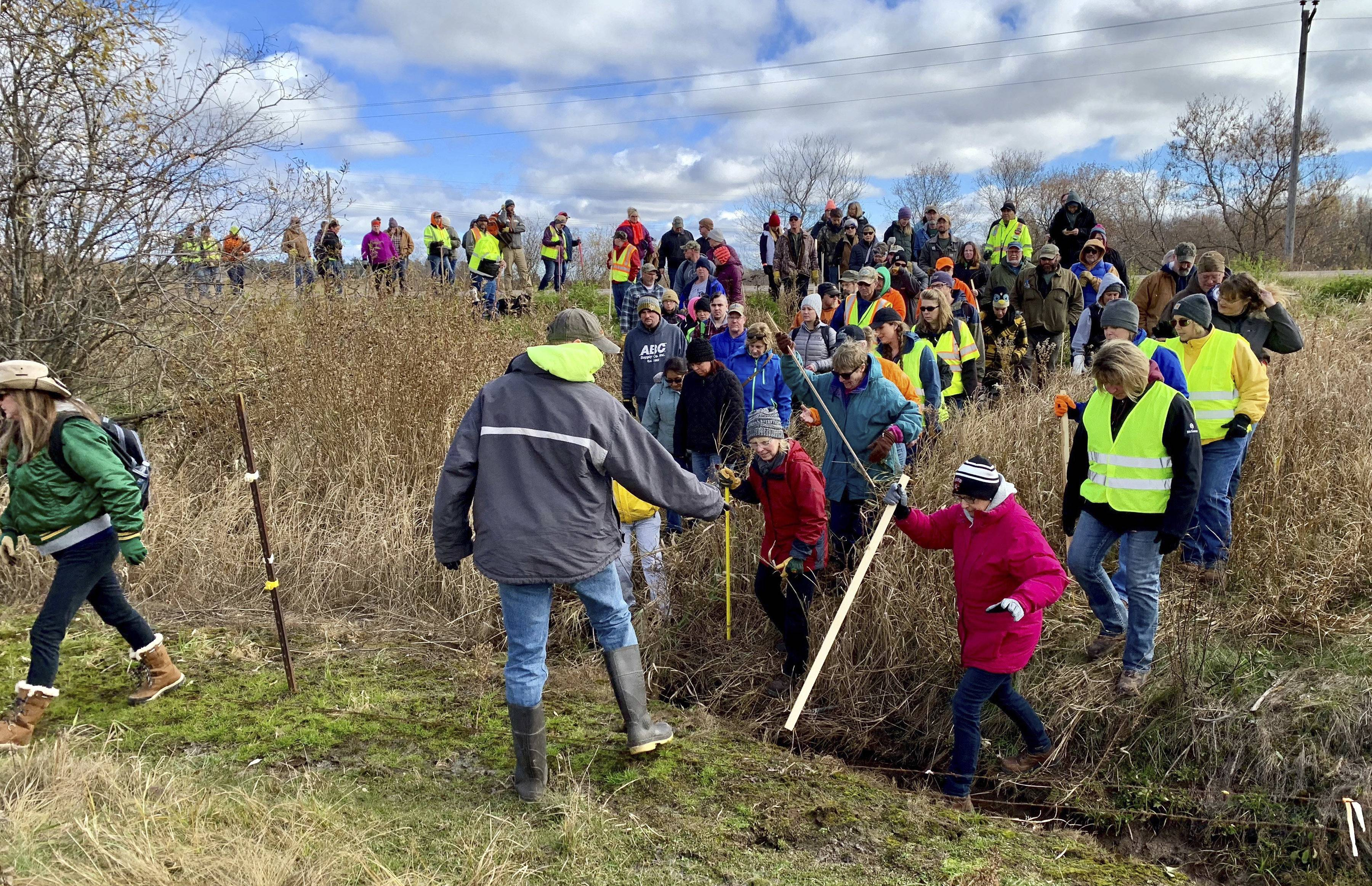 In this Oct. 23, 2018, file photo, volunteers cross a creek and barbed wire near Barron, Wis., on their way to a ground search for 13-year-old Jayme Closs who was discovered missing Oct. 15 after her parents were found fatally shot at their home. The Barron County Sheriff's Department said on its Facebook page that that the teenager Closs has been located Thursday, Jan. 10, 2019, and that a suspect was taken into custody.