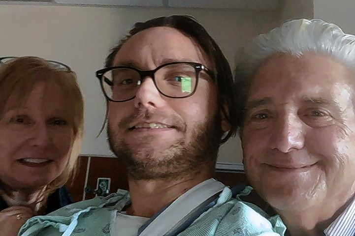 Stephen Casazza Jr., center, pictured with his parents at the hospital, is recovering after being shot three times New Year's Eve as he was delivering mail in Elk Grove Village.