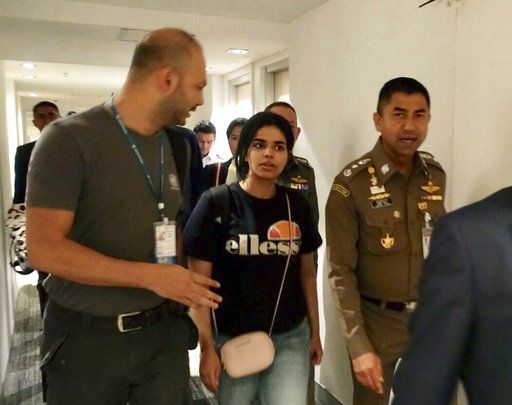 FILE - In this Jan. 7, 2019, file photo released by the Immigration Police, Chief of Immigration Police Maj. Gen. Surachate Hakparn, right, walks with Saudi woman Rahaf Mohammed Alqunun before leaving the Suvarnabhumi Airport in Bangkok, Thailand. Australia says it is considering granting the Saudi who fled from her family refugee resettlement based on referral by the U.N. (Immigration police via AP, File)