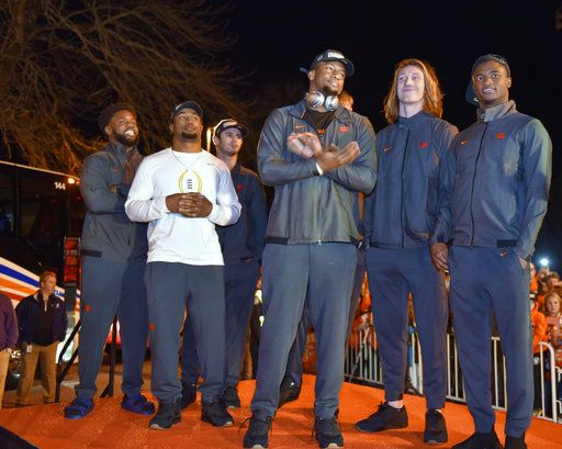 Clemson's Christian Wilkins, Adam Choice, Hunter Renfrow, Clelin Ferrell, Trevor Lawrence and Trayvon Mullen, from left, stand on a stage after the team returned to campus Tuesday, Jan. 8, 2019, in Clemson, S.C., the day after a 44-16 win over Alabama in the College Football Playoff championship game.