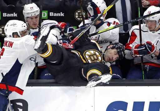 Boston Bruins defenseman Zdeno Chara is checked into the Washington Capitals bench by Washington Capitals left wing Alex Ovechkin, left, during the first period of an NHL hockey game Thursday, Jan. 10, 2019, in Boston.