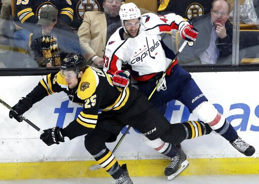 Boston Bruins defenseman Brandon Carlo (25) and Washington Capitals right wing Tom Wilson (43) fight for position along the boards in the third period of an NHL hockey game Thursday, Jan. 10, 2019, in Boston.