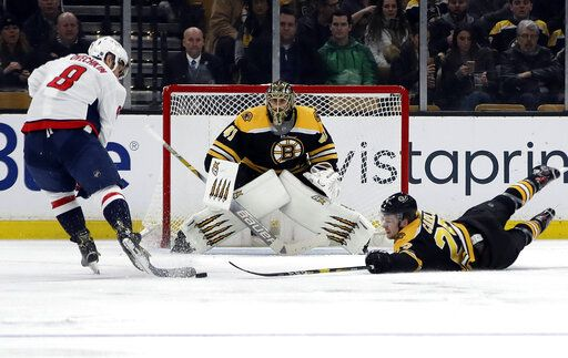 Boston Bruins defenseman Brandon Carlo, right, dives to prevent Washington Capitals left wing Alex Ovechkin (8) from scoring as Bruins goaltender Jaroslav Halak (41) protects the net during the second period of an NHL hockey game Thursday, Jan. 10, 2019, in Boston.