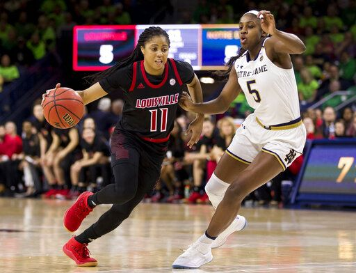 Louisville's Arica Carter (11) drives in next to Notre Dame's Jackie Young (5) during the first half of an NCAA college basketball game Thursday, Jan. 10, 2019, in South Bend, Ind.
