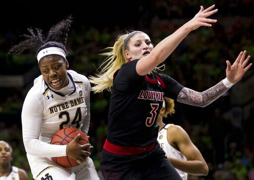 Notre Dame's Arike Ogunbowale (24) grabs a rebound next to Louisville's Sam Fuehring (3) during the first half of an NCAA college basketball game Thursday, Jan. 10, 2019, in South Bend, Ind.