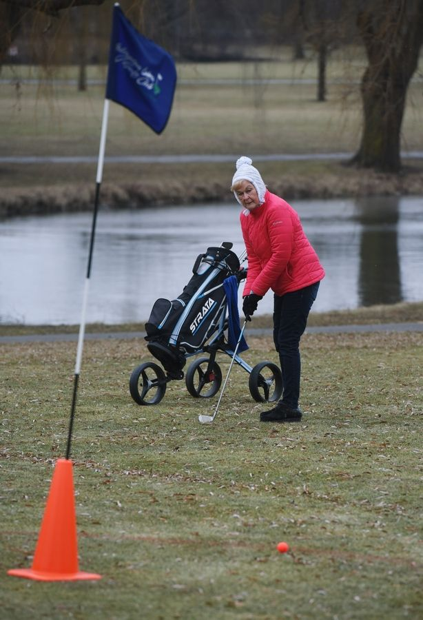 Jan Froberg of Mount Prospect hits her putt by getting her ball into the painted ring during the Chilly Open at Arlington Lakes Golf Club in Arlington Heights Saturday.