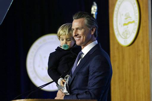 California Governor Gavin Newsom holds his son, Dutch, while speaking during his inauguration Monday, Jan. 7, 2019, in Sacramento, Calif.