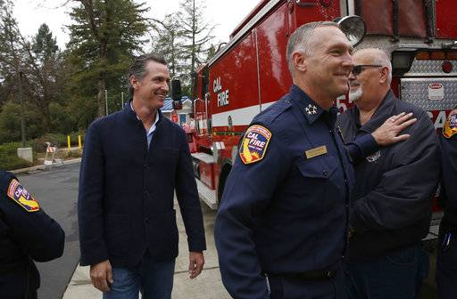 Gov. Gavin Newsom, left, is escorted by Thom Porter, right, to the California Department of Forestry and Fire Protection CalFire Colfax Station Tuesday, Jan. 8, 2019, in Colfax, Calif. On his first full day as governor, Newsom announced executive actions to improve the state's response to wildfires and other emergencies. Earlier Newsom appointed Porter, to head the state's firefighting agency.