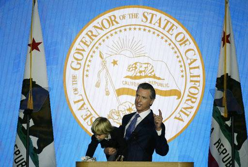 In this Monday, Jan. 7, 2019, photo, California Gov. Gavin Newsom holds his son Dutch while giving his address at his inauguration in Sacramento, Calif. Newsom gets his chance this week to show how he'll resolve a central tension in his platform: advancing expensive new programs while maintaining robust savings.
