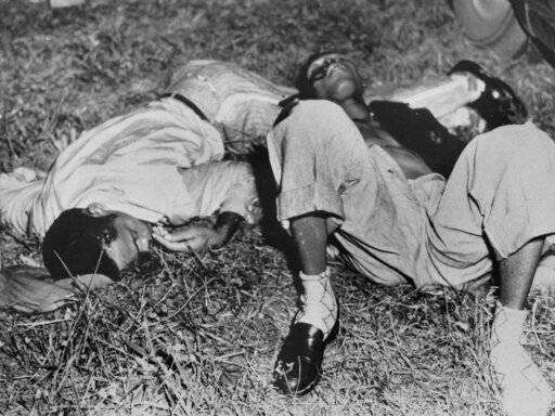 EDS NOTE: GRAPHIC CONTENT - In this Nov. 7, 1951, file photo, Samuel Shepherd, left, and Walter Lee Irvin, lie on the roadside near Umatilla, Fla., after they were shot by Lake County Sheriff Willis McCall, who claimed the handcuffed men tried to escape as he transferred them from prison to a jail. Shepherd was killed and Irvin critically wounded. Florida Gov. Ron DeSantis and a Cabinet granted posthumous pardons Friday, Jan. 11, 2019, to Shepherd, Irvin, Charles Greenlee and Ernest Thomas, the four African-American men accused of raping a white woman in 1949 in a case now seen as a racial injustice.