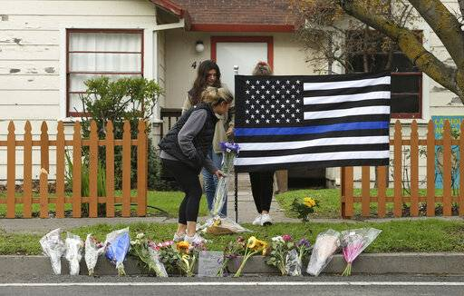 Sydney Carlier, foreground, accompanied by roommates, Jenna Brouwer, center and Camille Foder, behind flag, places flowers on a memorial for slain Davis Police Officer Natalie Corona, Friday, Jan. 11, 2019, in Davis, Calif. Corona, 22, who had been on the job only a few weeks, was shot and killed, Thursday, by a suspect who opened fire as she was investigating a three-car crash. The suspect was later found dead from a self-inflicted gunshot, following a standoff with officers.