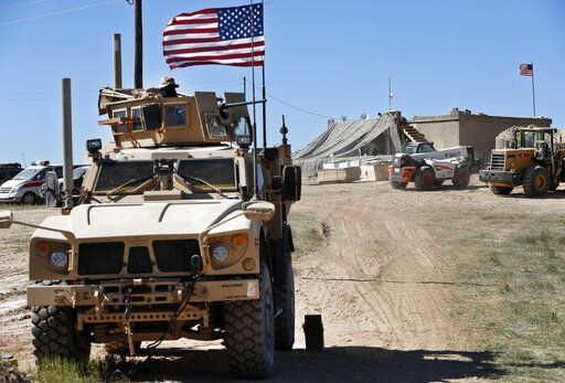 FILE - In this Wednesday, April 4, 2018 file photo, a U.S. soldier, left, sits on an armored vehicle behind a sand barrier at a newly installed position near the front line between the U.S-backed Syrian Manbij Military Council and the Turkish-backed fighters, in Manbij, north Syria. An American military official said Friday, Jan. 11, 2019 that the U.S.-led military coalition has begun the process of withdrawing troops from Syria.