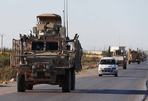 FILE - In this Saturday, March 31, 2018 file photo, a convoy of U.S. troops drive along a road leading to the front line with Turkish-backed fighters, in Manbij, north Syria. An American military official said Friday, Jan. 11, 2019 that the U.S.-led military coalition has begun the process of withdrawing troops from Syria.