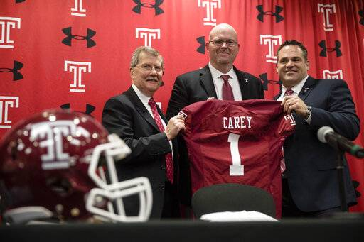 Temple University's President Richard Englert, left, and director of athletics, Patrick Kraft, right, pose for photographs with incoming head coach Rod Carey, center, speaks during an NCAA college football news conference in Philadelphia, Friday, Jan. 11, 2019.