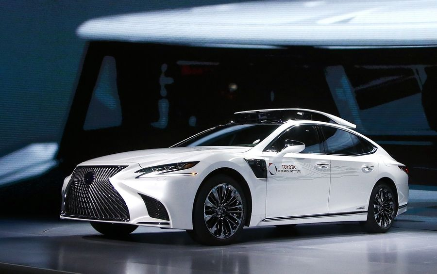 Toyota Research Institute, shows off Toyota's latest autonomous-driving test vehicle, called P4, based on the new-generation Lexus LS500h hybrid luxury sedan, with a roof-mounted assembly with cameras and sensors, and sensors added onto the front fenders, at the Toyota news conference at CES International Monday, Jan. 7, 2019, in Las Vegas.