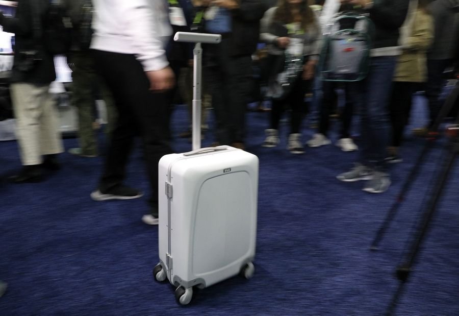 A man demonstrates the Ovis Suitcase at the ForwardX booth during CES Unveiled at CES International, Sunday, Jan. 6, 2019, in Las Vegas. The suitcase will automatically follow the user at their side as they walk.
