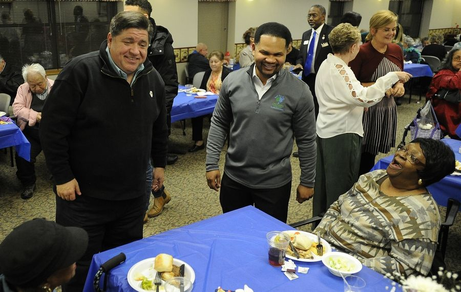 Gov.-Elect J.B. Pritzker and Aurora Mayor Richard Irvin greet the residents of the Lutheran Social Services of Illinois Senior Apartments, including Catherine Cross of Aurora on Saturday.