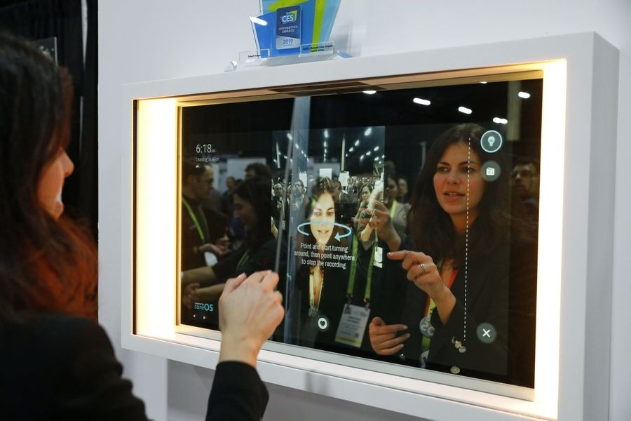 A woman demonstrates the Artemis smart mirror at the CareOS booth during CES Unveiled at CES International, Sunday, Jan. 6, 2019, in Las Vegas. The interactive mirror has video capture, virtual try-ons, facial and object recognition, and can give the user video instruction on specific makeup products, among other things.