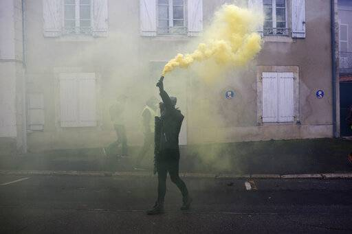 A protestor hold a smoke grande during a demonstration in Bourges, central France, Saturday, Jan. 12, 2019. Paris brought in armored vehicles and the central French city of Bourges shuttered shops to brace for new yellow vest protests. The movement is seeking new arenas and new momentum for its weekly demonstrations. Authorities deployed 80,000 security forces nationwide for a ninth straight weekend of anti-government protests.