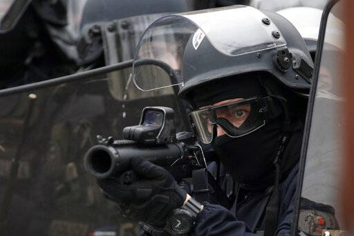 A police officer aims a flash ball gun during clashes with yellow vest protesters on the famed Champs Elysees avenue in Paris, France, Saturday, Jan. 12, 2019. Authorities deployed 80,000 security forces nationwide for a ninth straight weekend of anti-government protests.