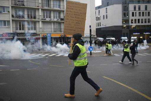 A yellow vest protestor holds a placard during clashes in Bourges, central France, Saturday, Jan. 12, 2019. Paris brought in armored vehicles and the central French city of Bourges shuttered shops to brace for new yellow vest protests. The movement is seeking new arenas and new momentum for its weekly demonstrations. Authorities deployed 80,000 security forces nationwide for a ninth straight weekend of anti-government protests.