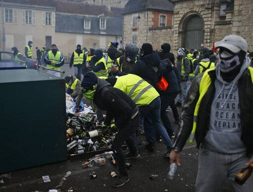 Yellow vest protestors break open a glass recycling container to arm themselves with glass bottles during clashes in Bourges, central France, Saturday, Jan. 12, 2019. Paris brought in armored vehicles and the central French city of Bourges shuttered shops to brace for new yellow vest protests. The movement is seeking new arenas and new momentum for its weekly demonstrations. Authorities deployed 80,000 security forces nationwide for a ninth straight weekend of anti-government protests.