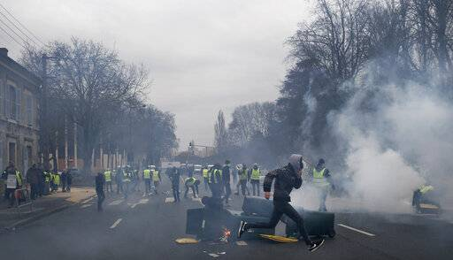 Yellow vest protestors set up barricades during a demonstration in Bourges, central France, Saturday, Jan. 12, 2019. Paris brought in armored vehicles and the central French city of Bourges shuttered shops to brace for new yellow vest protests. The movement is seeking new arenas and new momentum for its weekly demonstrations. Authorities deployed 80,000 security forces nationwide for a ninth straight weekend of anti-government protests.