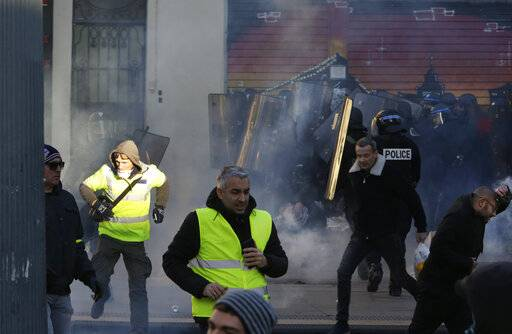 Yellow vest protestors run for cover as French riot police advances during a demonstration in Marseille, southern France, Saturday, Jan. 12, 2019. Paris brought in armored vehicles and the central French city of Bourges shuttered shops to brace for new yellow vest protests. The movement is seeking new arenas and new momentum for its weekly demonstrations. Authorities deployed 80,000 security forces nationwide for a ninth straight weekend of anti-government protests.