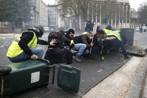 Yellow vest demonstrators take cover during clashes with French riot police during a demonstration in Bourges, central France, Saturday, Jan. 12, 2019. Paris brought in armored vehicles and the central French city of Bourges shuttered shops to brace for new yellow vest protests. The movement is seeking new arenas and new momentum for its weekly demonstrations. Authorities deployed 80,000 security forces nationwide for a ninth straight weekend of anti-government protests.