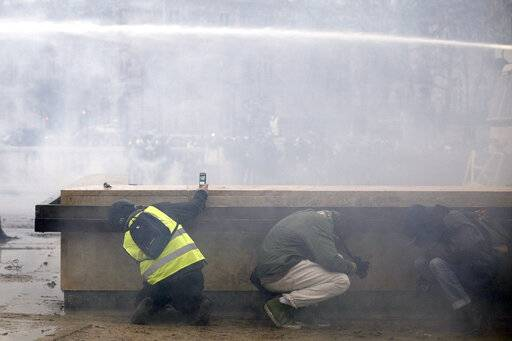 Yellow vest protesters take shelter as riot police use a water canon during clashes around the Arc of Triomphe, in Paris, France, Saturday, Jan. 12, 2019. Authorities deployed 80,000 security forces nationwide for a ninth straight weekend of anti-government protests.