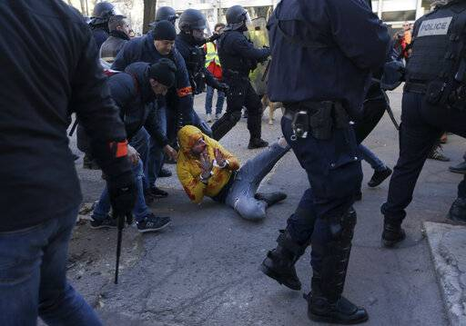 French plainclothes police drag a bleeding, handcuffed protestor, during a yellow vest demonstration in Marseille, France, Saturday, Jan. 12, 2019. Paris brought in armored vehicles and the central French city of Bourges shuttered shops to brace for new yellow vest protests. The movement is seeking new arenas and new momentum for its weekly demonstrations. Authorities deployed 80,000 security forces nationwide for a ninth straight weekend of anti-government protests.