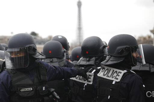 Riot Police take position during clashes with yellow vest protesters around the Arc of Triomphe, in Paris, France, Saturday, Jan. 12, 2019. Authorities deployed 80,000 security forces nationwide for a ninth straight weekend of anti-government protests.